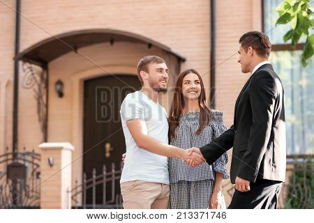 Young couple with real estate agent near house