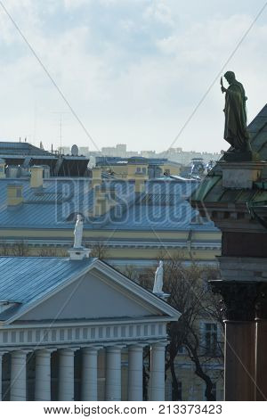Sculpture of Apostle Bartholomew on roof of St. Isaac Cathedral and sculptures at Horse Guards Manege building in St. Petersburg, Russia