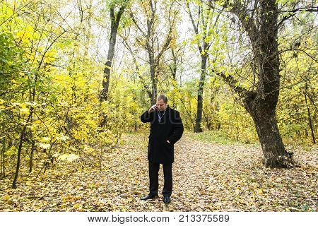 Handsome Young Man With A Smartphone On The Street Talking In The Park.