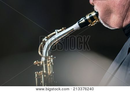 The saxophonist plays music on a dark background. Backlight. Blur.