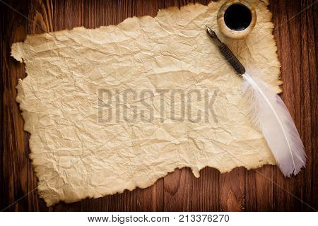 Quill With Inkstand On Vintage Paper Background And Wood Table