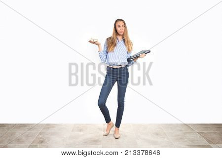 Young mom in business clothes trying to balance work and family life, holding booties and documents, making tough choice