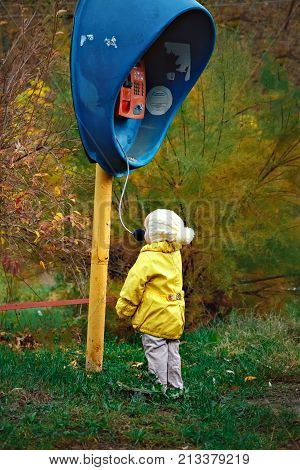 a little girl in a yellow coat talks on an old payphone