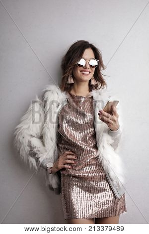 Woman with fashionable clothes holding a smartphone
