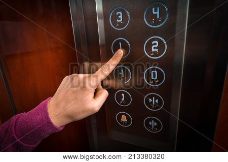 Woman pressing the button in the modern elevator interior
