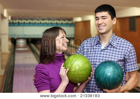 Young man and girl hold balls for bowling and laugh merrily