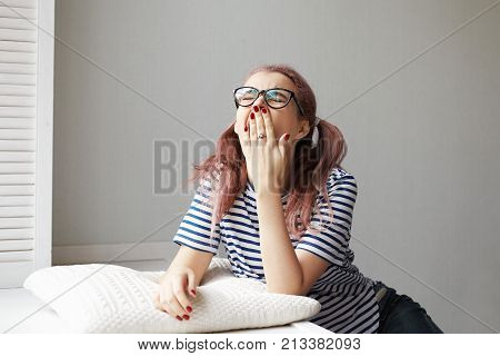 Boredom and fatigue concept. Picture of trendy looking student girl in glasses throwing head back and yawning covering mouth with hand feeling sleepy and tired after sleepless night out with friends