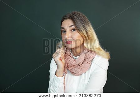 Doubt hesitation and suspicion concept. Isolated shot of mature blonde female wearing stylish pink scarf having skeptic uncertain facial expression thinking about some offer decision or idea