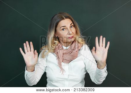 Portrait of confident determined elderly woman with blonde grey hair making stop gesture showing open palms at camera meaning: Stay away from me Don't come close. Body language signs and symbols