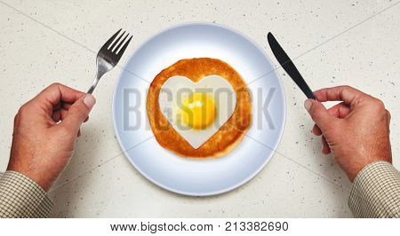 tableware in hands of man and scrambled egg on plate