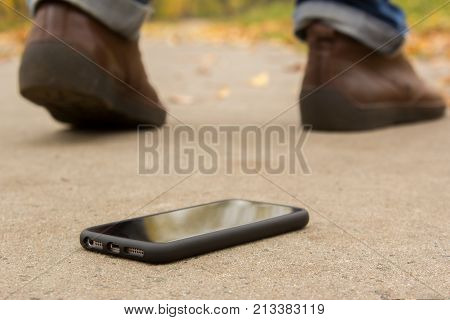 The man lost the phone. Men leave and only the legs and shoes are not in focus and the phone on the ground