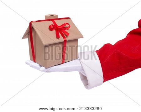 Santa gives as a gift a house. A Santa's hand holds a wrapped house gift with a red ribbon. Present for the New Year
