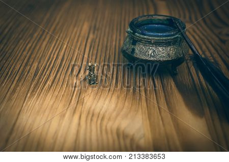 Feather pen inkwell and small toy mouse isolated on wooden table background. Education background.
