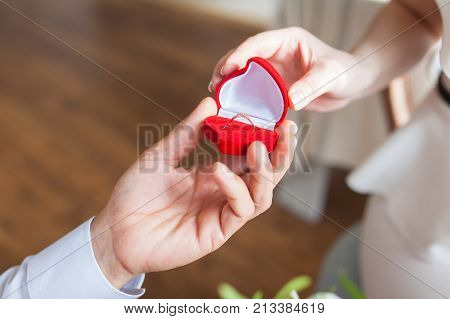 Male hands with red velvet box containing engagement ring with brilliant