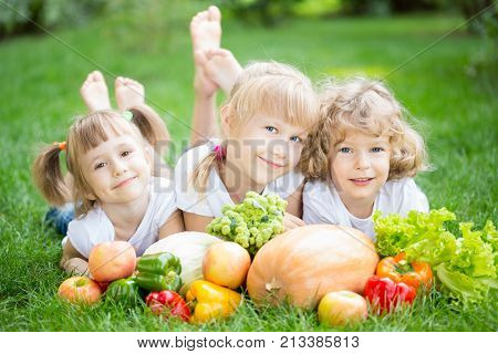 Group of happy children with fruits and vegetables lying on green grass in spring park. Healthy lifestyles concept