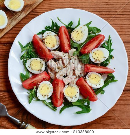Fresh vegetable salad with chicken breast and quail eggs. Salad with tomatoes, rucola, quail eggs, chicken breast and spices on a plate and a wooden background. Healthy nutrition. Closeup. Top view