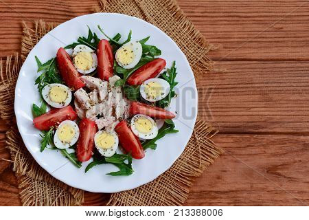 Green vegetable salad, chicken and quail eggs. Salad with tomatoes, arugula, quail eggs, chicken fillet and spices on a plate and a wooden background with copy space. Healthy and tasty food. Top view