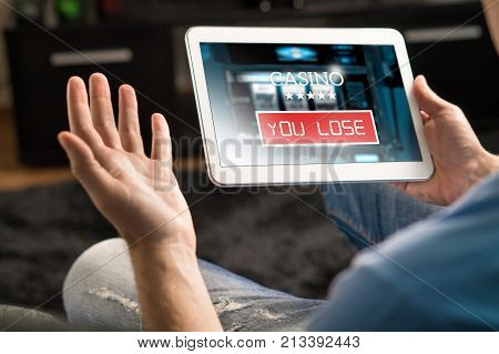 Losing Money In Online Casino. Man Playing Online Slot Machine Game With Tablet.