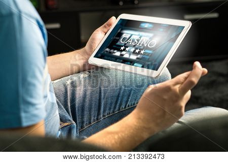 Excited Man Playing In An Online Casino With Tablet Fingers Crossed Wishing And Hoping To Win.