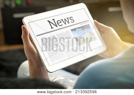 Man reading the news on tablet at home. Imaginary online and mobile news website application or portal on modern touch screen display. Holding smart device in hand.