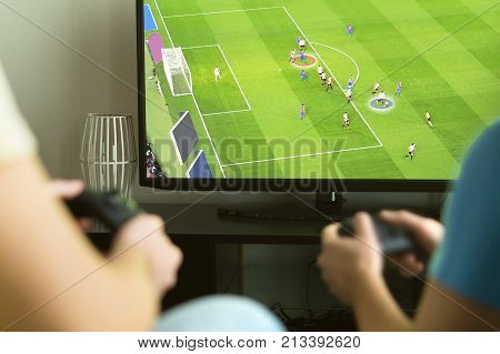 Two Guys Playing Imaginary Multiplayer Soccer Or Football Video Game With Console And Tv.