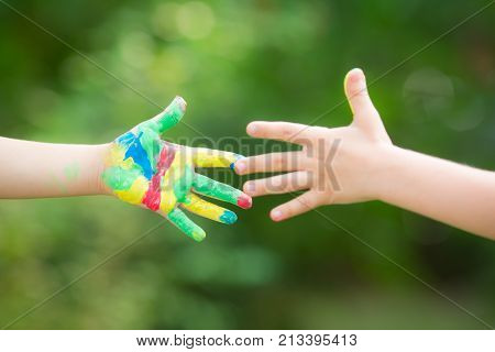 Handshake with painted hands against green spring background