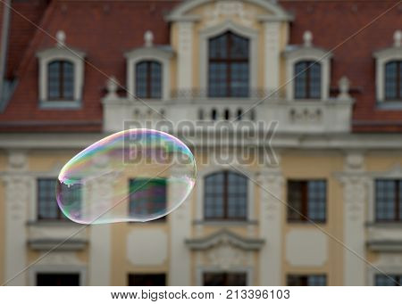 A Single Big Soap Bubbles In Front Of An Old House