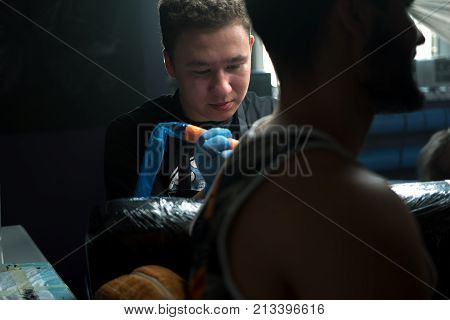Male tattooist wearing sterile gloves tattooing young man. Professional tattoo gun, working process