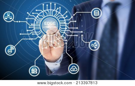 IT expert in a blue suit clicks on a circuit diagram with the words edge computing surrounded by specific icons
