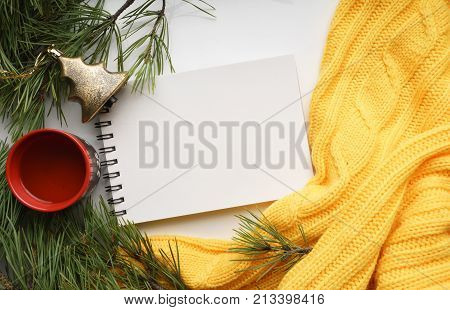 Christmas background with a Cup  of tea, a notebook, Christmas toys, branches of pine with large needles and a yellow sweater. Top view, close-up