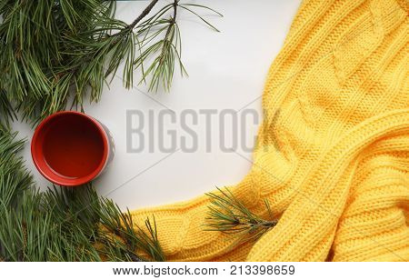 Christmas background with a Cup  of tea,  branches of pine with large needles and a yellow sweater. Top view, close-up