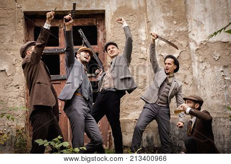 A group of gangsters with various dangerous weapons in their hands amidst an old abandoned building, they are celebrating something by raising their arms above their heads. Retro. On open air.