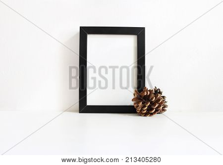 Black vertical blank wooden frame mockup with pine cones lying on the white table. Poster product design. Styled stock feminine photography. Home decor, Christmas winter concept.