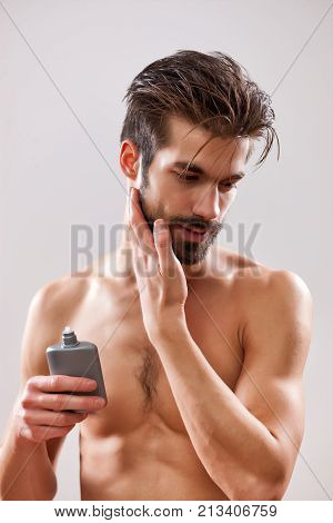 Young man is applying aftershave to his face.