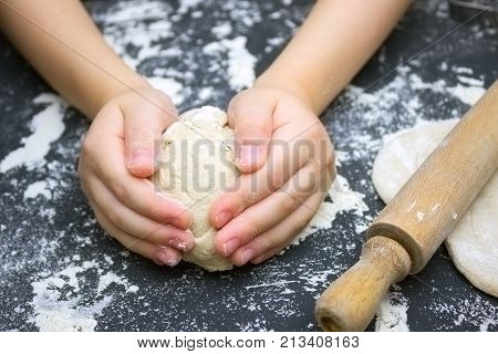 Kid's hands some flour wheat dough and rolling pin on the black table. Children hands making the rye dough for backing bread. Small hands kneading dough. Little child preparing dough for backing
