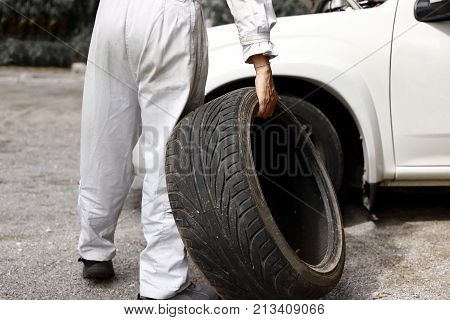 Professional automotive mechanic in uniform holding tire for fixing car at the garage background. Auto repair service.