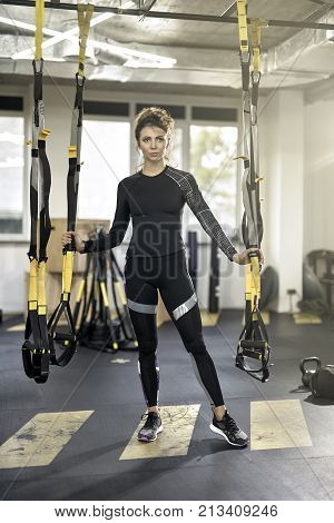 Thoughtful girl is posing between hanging TRX straps in the gym on the windows background. She wears a dark sportswear with sneakers. Woman holds her hands on the straps. Vertical.