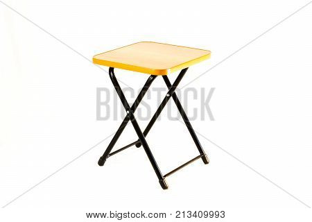 The small square stool on the white background. The stool is isolated on white and a clipping path is provided for easy extraction. The stool is portable and it is ideal for picnic and outing.