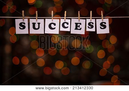 Success text on papers with clothespins with garland bokeh on background. The word