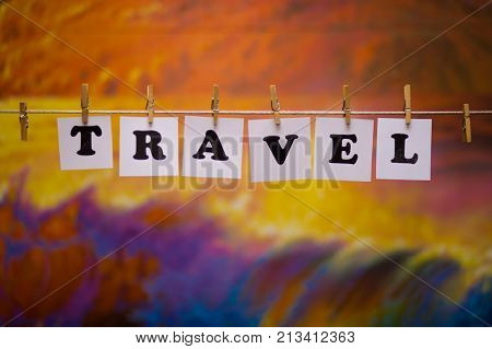 Travel text on papers with clothespins with garland bokeh on background. The word