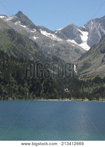 Blue lake between mountains, snow and trees