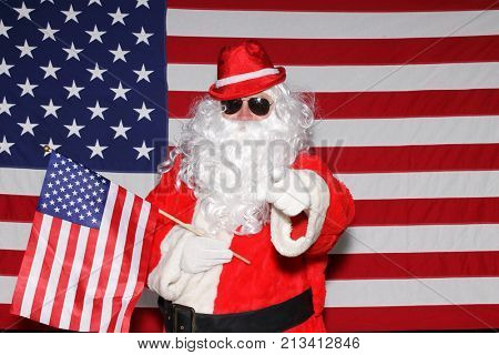 Santa Claus poses in front of an American Flag.  Santa points at you the viewer while holding an American Flag/