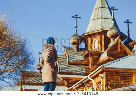 a woman looks at a wooden Church in Russia