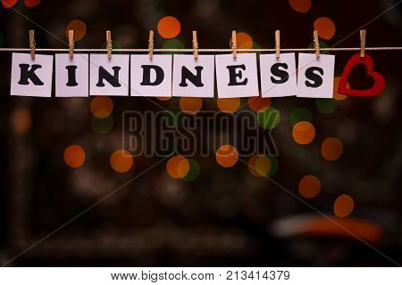 Kindness text on papers with clothespins with garland bokeh on background. The word
