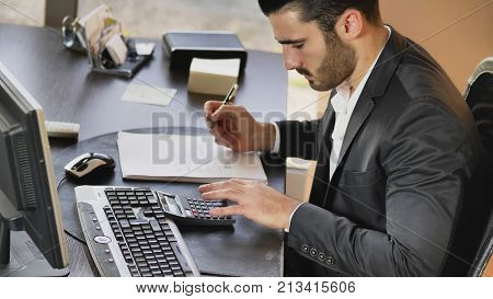 Confident man in formal wear working as accountant at desktop taking notes while using calculating machine.