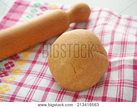 Preparing dough for gingerbread, cookies, shortbread, cakes, pastries, or pizza. Leavened dough in a shape of ball upon rustic table. Preparing Christmas treat.