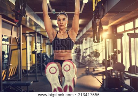 Girl on training in gym pulls up on bar and exercises six pack