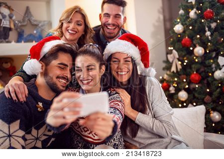 happy smiling friends taking photo with mobile phone for Christmas