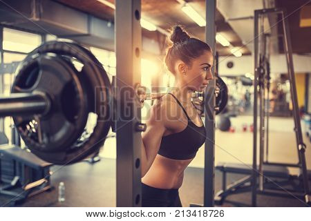 Fit beautiful girl doing squats with barbell in gym