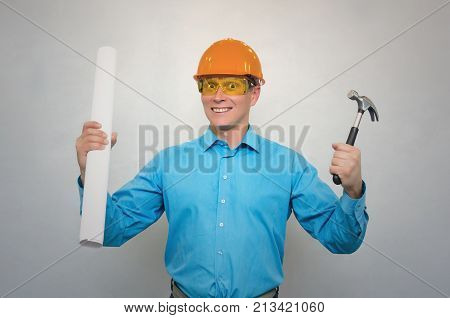 Young happy engineer worker in a helmet holding in one hand project drawings and hummer in another hand isolated. Construction.